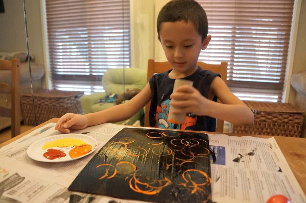 Painting and stamping a background for recycled robot art